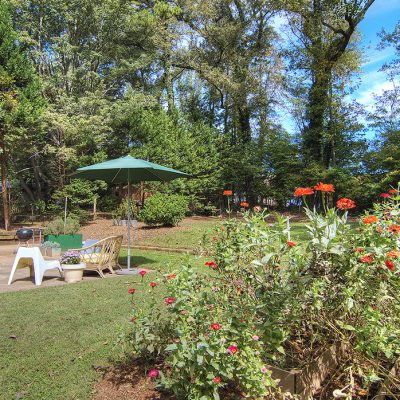 lovely back yard with patio and raised flower garden beds