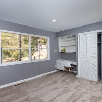 Guest bedroom with double closet, built in desk and expansive windows